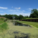 Левое крыло казарм и ров с водой на территории форта №11.